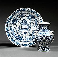 PLAT en porcelaine et bleu de cobalt sous couverte, monté sur un petit talon, le contour circulaire, à décor, sur le bassin, de cinq...