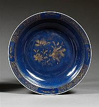 ƒPLAT CREUX en porcelaine, couverte monochrome bleu poudré et dorure, monté sur un petit pied, de contour circulaire, à décor, sur l...