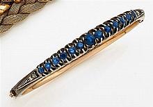 Bracelet rigide ouvrant orné d'une ligne de saphirs de taille dégressive en chatons à griffes et de petits diamants taillés en rose....