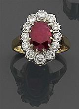 Bague rubis entourage Elle est ornée d'un rubis ovale dans un entourage de diamants taille brillant. Monture en ors de deux tons. Po...