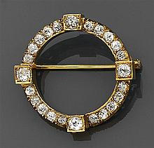 Broche en forme de cercle en or sertie de diamants taille brillant (TA). Elle porte quatre diamants plus importants en sertissure ca...