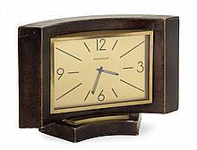 JAEGER LECOULTRE ANNEES 40 Pendulette de bureau en laiton dans un encadrement arrondi gainé de cuir. Cadran doré avec index peints. ...