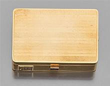 Poudrier de forme rectangulaire en or jaune guilloché à bandes. Un saphir baguette au fermoir. A l'intérieur un miroir. Monogrammé G...