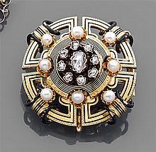 Broche ronde en or jaune ajouré ornée de filets d'émail noir. Elle est réhaussée de motifs ronds sertis de diamants taillés en rose ...