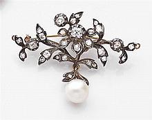 Broche florale rehaussée de diamants taille brillant (TA) retenant une perle de culture en pampille. Monture en or jaune et argent. ...