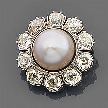 Broche perle fine Elle est de forme ronde portant au centre une grosse perle bouton dans un entourage de diamants taille brillant (T...