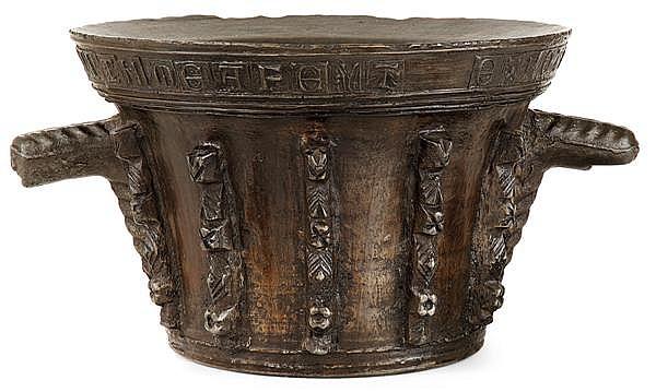 IMPORTANT MORTIER à dix ailettes en bronze disposées de chaque côté de deux prises à l'extrémité en tête humaine, il porte un texte ...