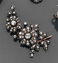 Broche branche fleurie composée de deux fleurs et de feuillages entièrement pavés de diamants taillés en rose montés à fond. Monture...