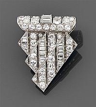 BOUCHERON Années 1930 Clip écusson Il est de forme triangulaire à rouleau à décor de rubans sertis de lignes de diamants taille bril...