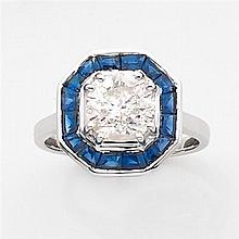 Bague hexagonale ornée au centre d'un diamant taille brillant dans un entourage de saphirs calibrés sertis en chatons à griffes. Mon...