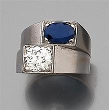 Bague chevalière en or gris à deux corps décalés, l'un serti d'un diamant taille brillant et l'autre d'un saphir ovale. Poids brut :...