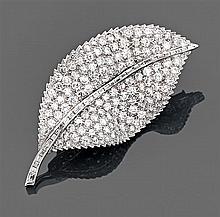 Broche feuille Elle est de forme ondulée entièrement pavée de diamants taille brillant la nervure soulignée de diamants baguettes. M...