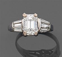 Bague diamant solitaire Elle est ornée d'un diamant taille émeraude rectangulaire les épaules sont serties chacune de trois diamants...