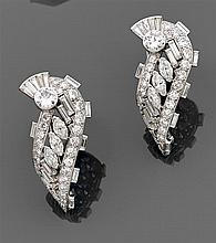 Paire de clips de revers en forme de volute en platine ajouré. Au centre des diamants navettes et baguettes. Pavage de diamants tail...