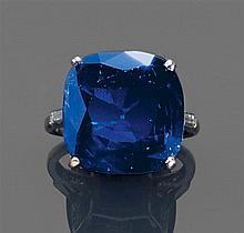 Bague saphir Elle est ornée d'un saphir de taille coussin. La monture est sertie de petits diamants ronds et de diamants baguette. M...