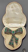 Grand devant de corsage en forme de nœud de ruban repercé et articulé. Il est rehaussé d'émeraudes rectangulaires en sertissure sur ...