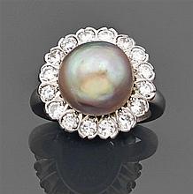 Bague perle fine Elle est ornée d'une perle fine bouton de couleur mordorée dans un entourage de diamants taille brillant. Monture e...