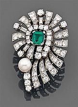 Broche tourbillon ajourée ornée au centre d'une émeraude à pans coupés sertie à griffes dans un entourage rayonnant de diamants tail...