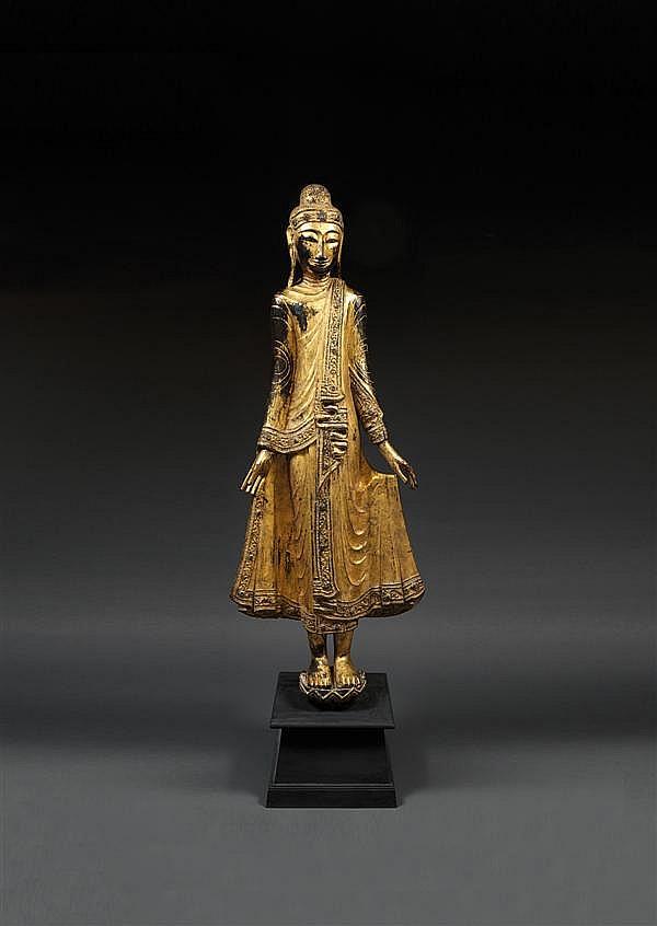 GRANDE STATUE en bois laqué, doré et applications de verroterie, représentant le Bouddha en pied sur un socle lotiforme, les yeux mi-cl