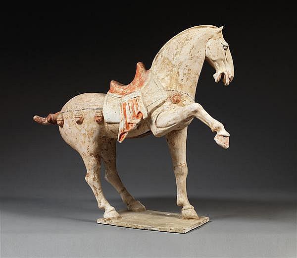 GRAND MINGQI en terre cuite et engobes blanc et rouge, représentant un cheval dansant richement harnaché et sellé, la tête légèrement c