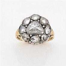 Bague en or jaune et argent ornée d'un diamant taillé en rose entouré de petits diamants taillés en rose