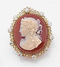 Broche camée Elle porte un camée sur cornaline de forme ovale représentant un profil de femme. Riche entourage de diamants taille br...