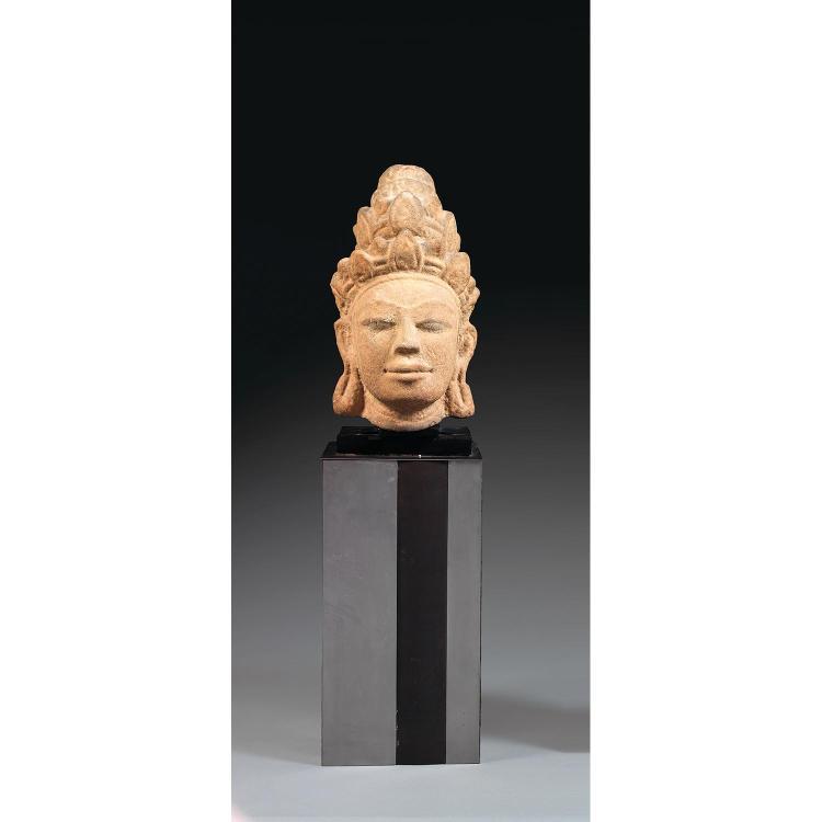 TÊTE DE DIVINITÉ en grès beige, représentée le visage serein et les yeux en amande, coiffée d'un important couvre-chef à étages soul...