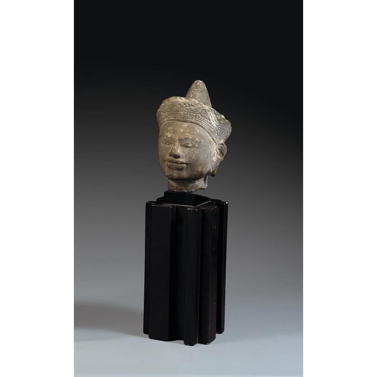 TÊTE DE DIVINITÉ en grès gris, représentée le visage serein et les yeux en amande, coiffée d'un couvre-chef à bandeau sculpté en lég...