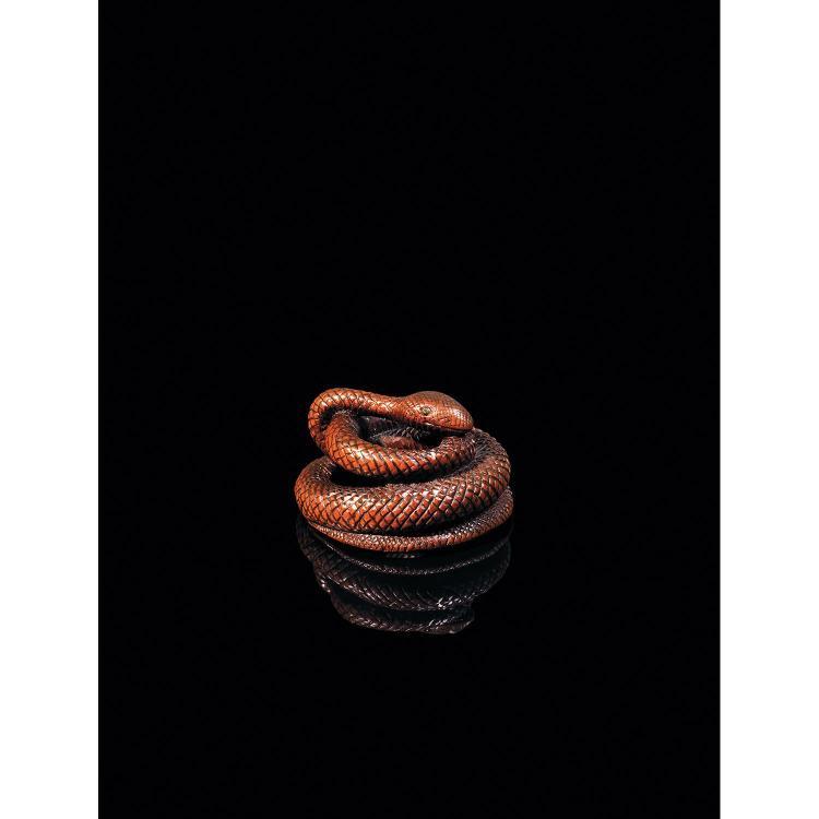 INTÉRESSANT NETSUKE en bois de belle patine, en forme de serpent enroulé sur lui-même, ses écailles suggérées au moyen d''une résille...
