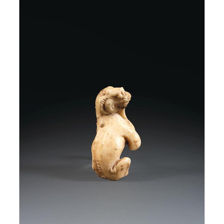 STATUETTE FRAGMENTAIRE DE LION en marbre beige comportant des traces d''enfouissement, représenté assis, la tête tournée vers la droi...
