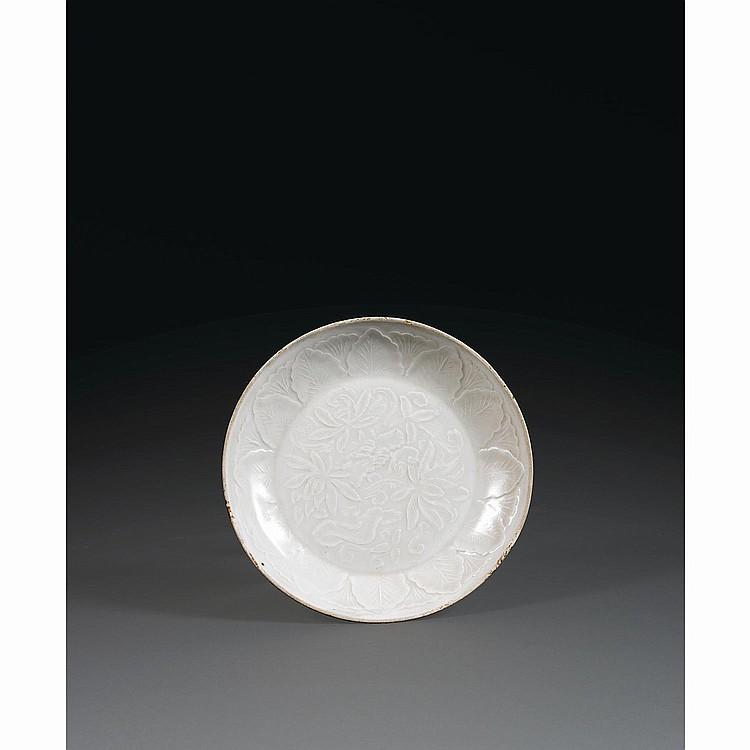 PETITE COUPE en porcelaine de Dingyao, à décor, moulé sous la couverte crème, de pivoines et feuilles disposées en frise sur l''aile....