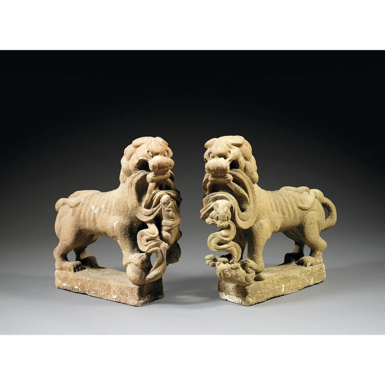 COUPLE DE LIONS BOUDDHIQUES en grès rose, représentés à l''arrêt sur une terrasse rectangulaire, la tête dans le prolongement du corp...