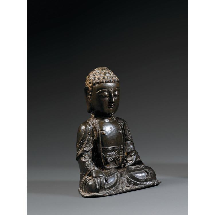 STATUETTE DE BOUDDHA en bronze de patine sombre, assis en vajrasana, la main droite en bhumisparsamudra, la gauche en varadamudra, v...