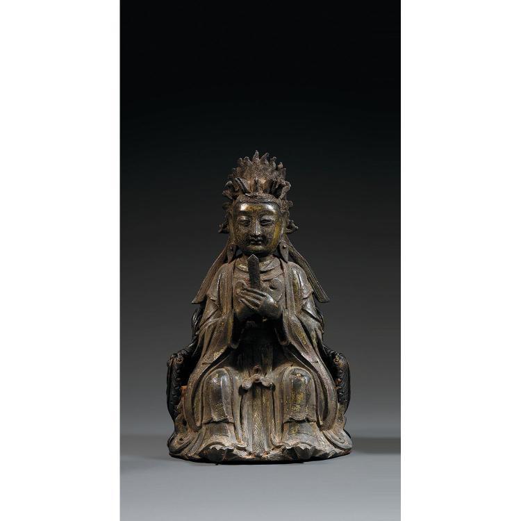 STATUETTE DE XIWANGMU en bronze autrefois laqué, représentée assise, les mains tenant une plaquette de jade, vêtue d''une robe galonn...