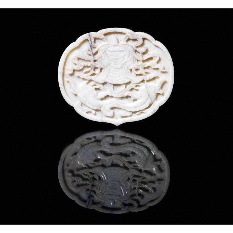 PLAQUE DE SCEPTRE en jade néphrite beige veiné de noir, de forme polylobée, à décor, sculpté en méplat, de deux poissons sous un dais.