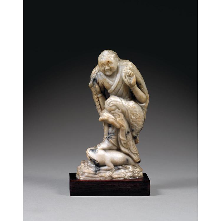 STATUETTE DE LIU HAI en stéatite grise infusée d''anthracite, représenté dansant sur le crapaud à trois pattes étendu sur des roches ...