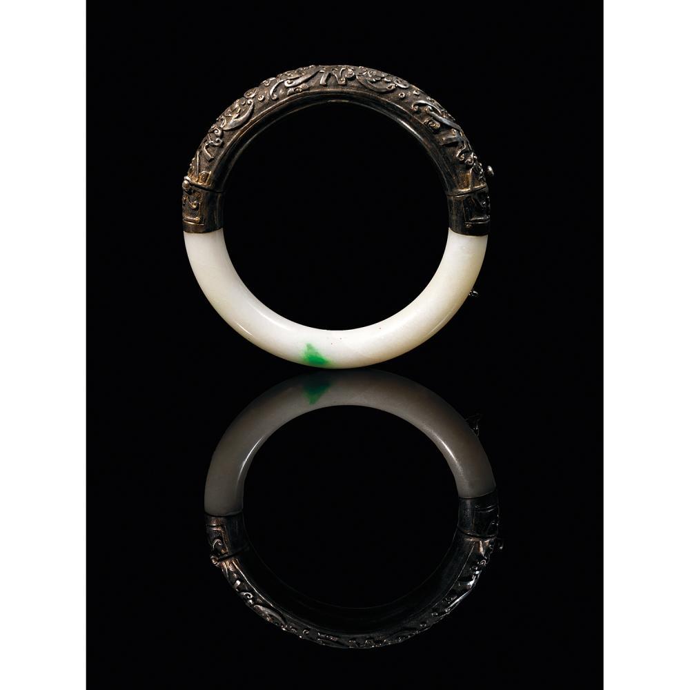 BRACELET JONC en jadéite blanc céladonné éclaboussé de vert pomme et argent, à décor de caractères auspicieux parmi les chauves-sour...