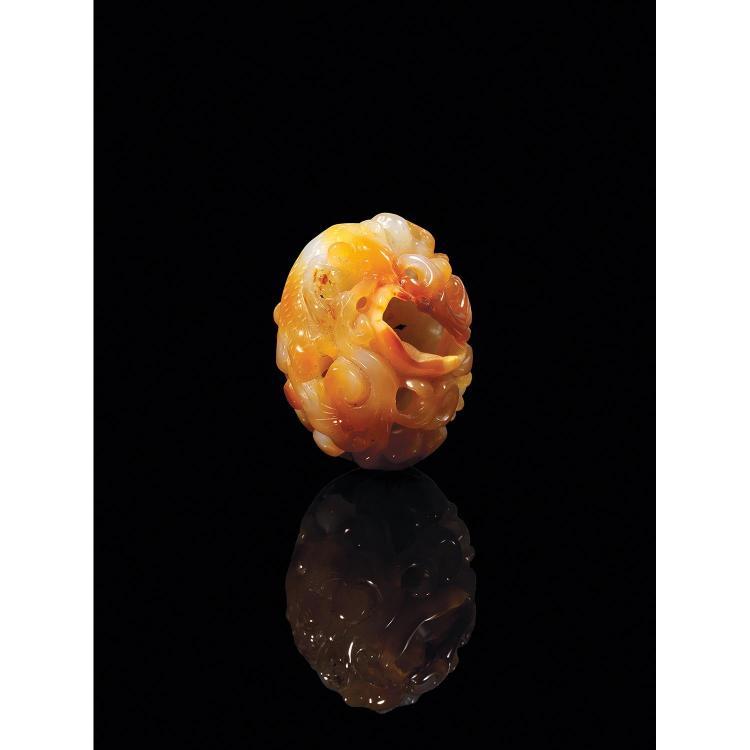GALET en agate beige veiné de rouille et de gris, à décor sculpté et ajouré d''un toupaye sur une feuille de lotus parmi les lingzhi.