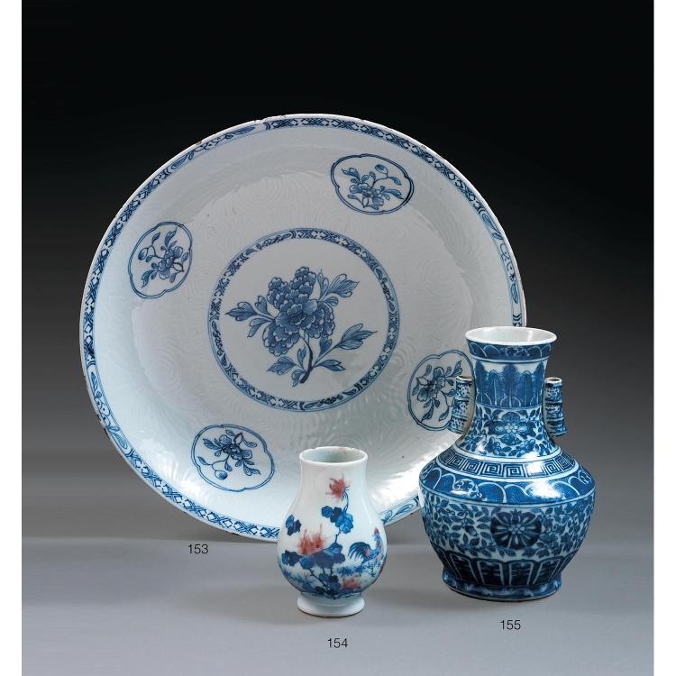 GRAND PLAT en porcelaine et bleu de cobalt sous couverte, monté sur un petit talon, de forme circulaire, la paroi évasée, à décor, s...