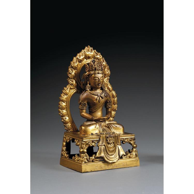 STATUETTE D''AMITAYUS INSCRITE en bronze doré, représenté assis en vajrasana sur une base quadrangulaire ajourée devant une mandorle,...