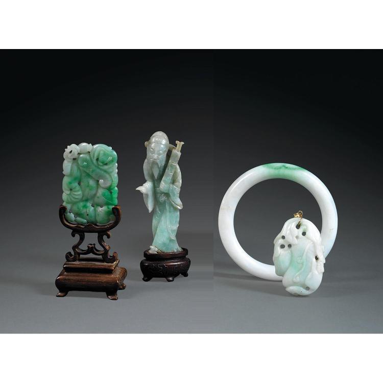 SUITE DE QUATRE OBJETS en jadéite blanc céladonné infusé de vert, comprenant deux pendentifs à décor de fruits et lingzhi, un bracel...