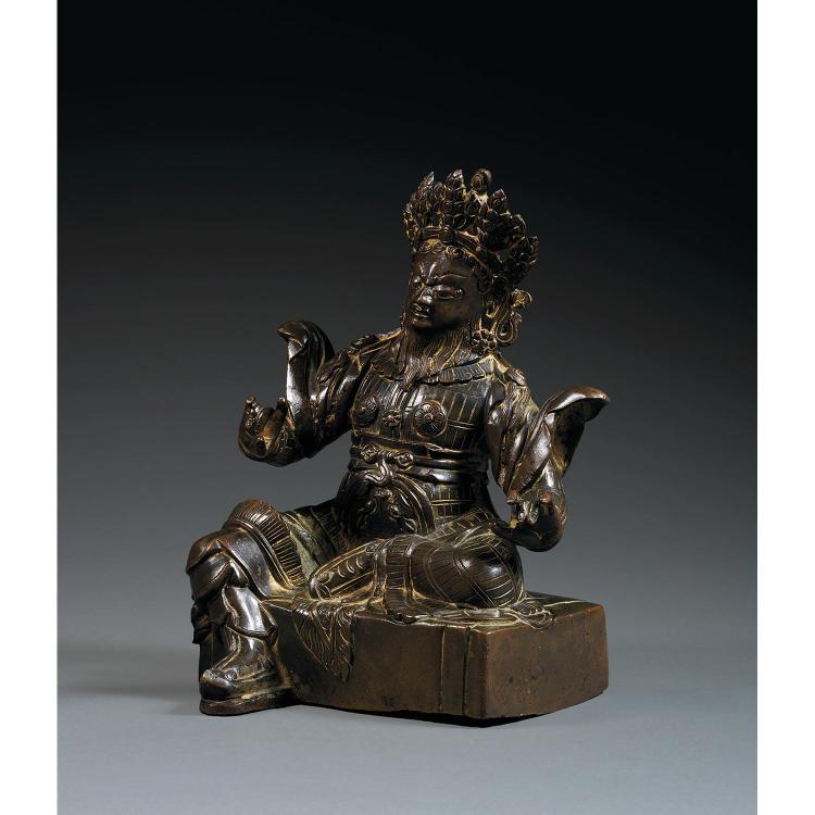 STATUETTE DU ROI DU CIEL VIRUDHAKA en bronze de patine sombre autrefois laqué et doré, représenté assis en ardhaparyanka sur une ter...
