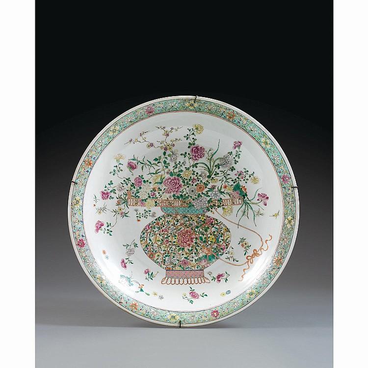GRAND PLAT en porcelaine, émaux polychromes dans le style de la famille rose et dorure, monté sur un petit talon, de contour circula...