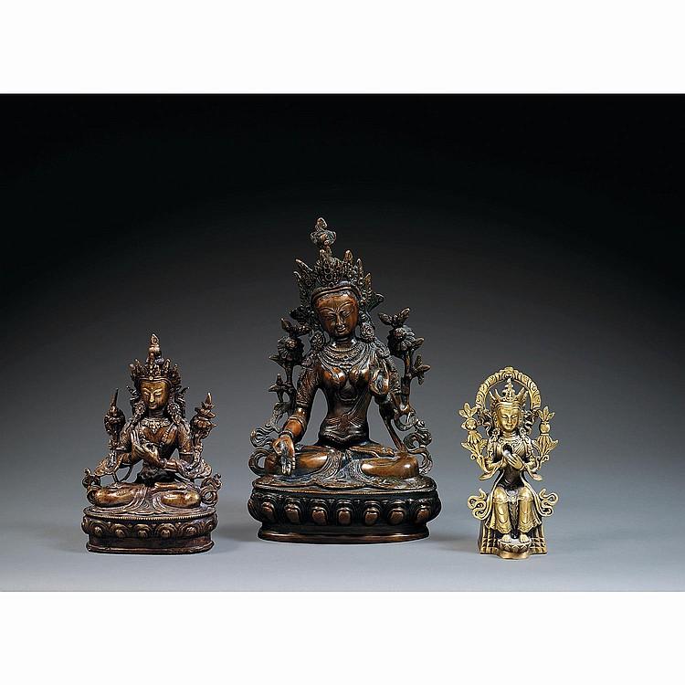 LOT DE TROIS STATUETTES en bronze, dont deux de patine sombre, comprenant une grande Tara blanche et un Boddhisattva, tous deux assi...