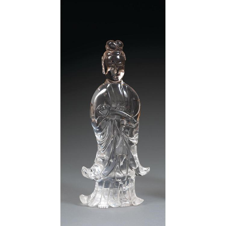 STATUETTE DE GUANYIN en cristal de roche, représentée debout, vêtue d''une ample robe, un sceptre ruyi dans les mains, les cheveux co...