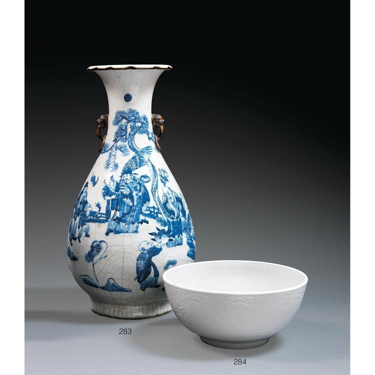 GRAND BOL en porcelaine et couverte blanche, monté sur un petit talon, la panse hémisphérique, à décor moulé sur la paroi extérieure...