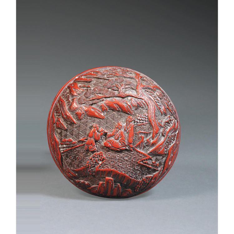 BOÎTE COUVERTE en laque rouge sculptée, de forme circulaire, à décor d''une scène animée de personnages dans un paysage sur fond d''un...