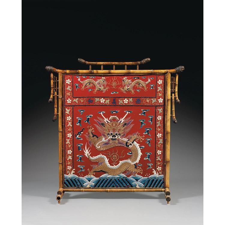 ÉCRAN FORMANT PARE-ÉTINCELLES la structure en bambou encadrant un panneau de drap de laine rouge, à décor brodé aux fils polychromes...
