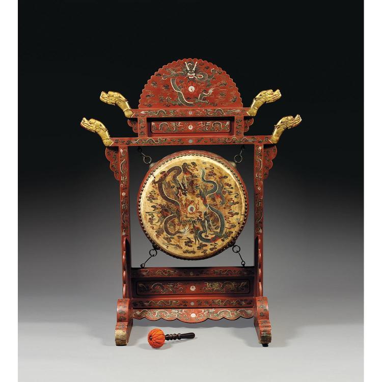 GRAND TAMBOUR SUR CADRE YONGGO ET SON PORTIQUE en bois laqué rouge, les montants terminés par des têtes de dragons dorées, à décor d...