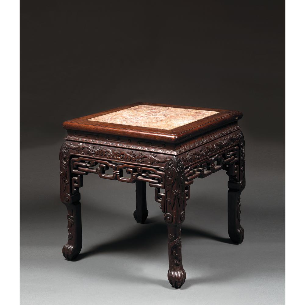 TABOURET OU TABLE BASSE en bois naturel, reposant sur quatre pieds griffes, à décor, sculpté en léger relief, de lotus et d'enroulem...